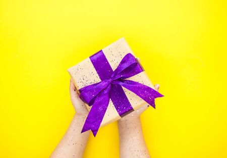 Childs hands holding giftbox tied with purple color ribbon on bright yellow background with glitter. Flat lay style.