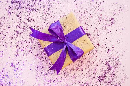 Giftbox tied with purple color ribbon on bright pink background with glitter. Flat lay style. Stock Photo
