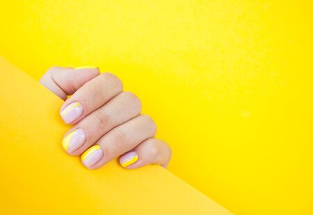 Young woman's hand with beautiful manicure on yellow color background holding bright yellow paper.