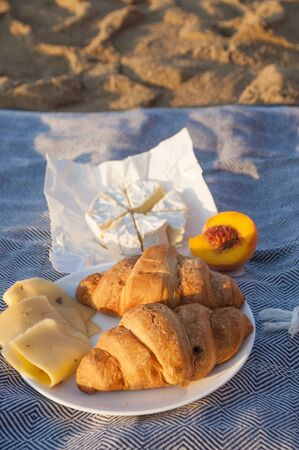 Summer picnic on the beach by the sea at a sunrise. Фото со стока