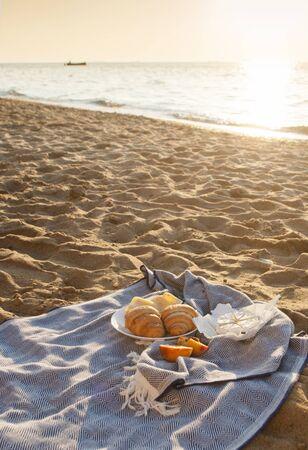 Picnic on the beach at a sunrise. Summer vacation. Фото со стока