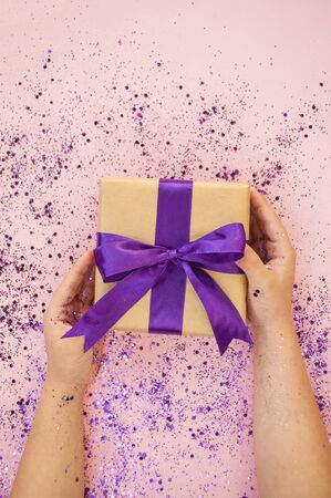 Childs hands holding gift box tied with purple color ribbon on pink background with glitter. Flat lay style.