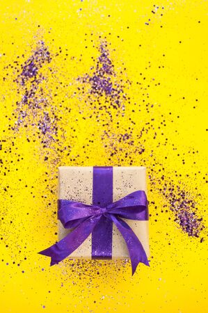 Giftbox tied with purple color ribbon on bright yellow background with glitter. Flat lay style.