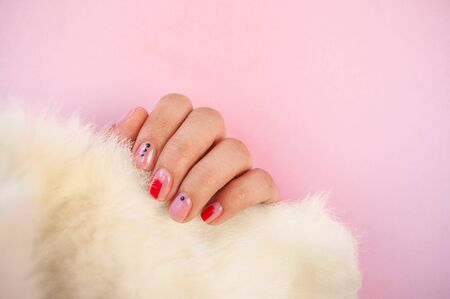 Young womans hand with beautiful manicure on pink color background holding piece of white faux fur. Archivio Fotografico - 133375424