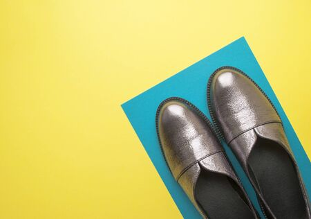 Pair of sparkly female shoes on yellow and blue background with copyspace. Flat lay style.