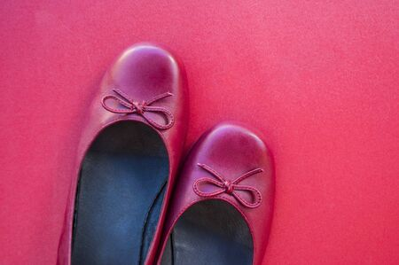 Stylish female flat shoes in dark red color on dark red background. Beauty and fashion concept.