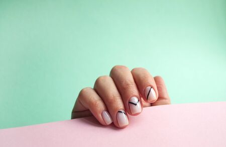 Young womans hand with beautiful manicure on pastel blue and turquoise background with copyspace.