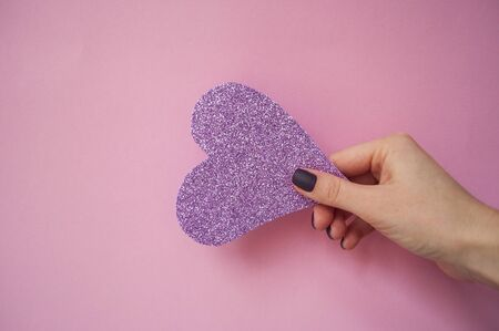 Young womans hand with beautiful manicure on pink background holding pink glittering heart.