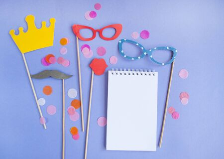 Colorful photo booth props crown, moustaches, glasses and lips on purple background with colorful confetti and copyspace. Set of party props.