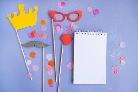Colorful photo booth props crown, moustaches, glasses and lips on purple background with colorful confetti and copyspace. Set of party props. Stock Photo