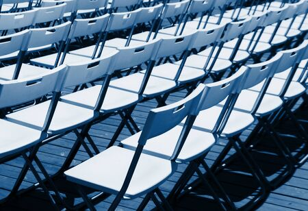 Rows of white empty folding chairs in a summer theatre. 2020 color trend. Banco de Imagens