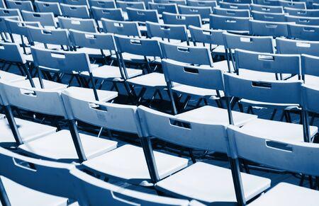 Filas de sillas plegables vacías blancas en un teatro de verano. Tendencia de color 2020. Foto de archivo
