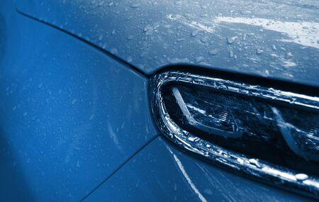 Beautiful rain drops on the car of trendy blue. Wet car body of trendy blue color. 2020 color trend.