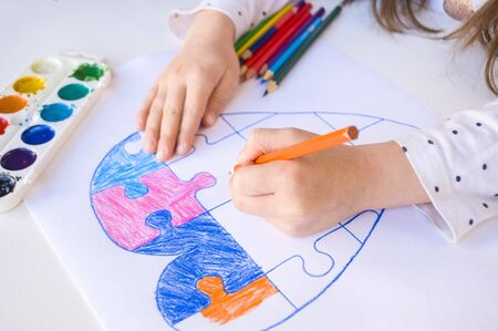 A child is drawing colorful heart with jigsaw puzzle on white background as a symbol of autism, with colorful pencils and watercolors.