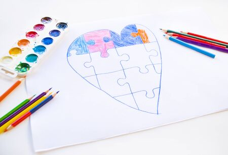 Colorful child drawn heart with jigsaw puzzle on white background as a symbol of autism, with colorful pencils and watercolors.