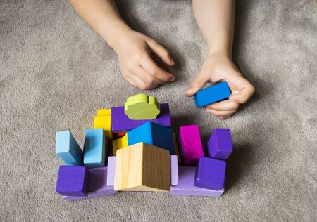 A child is playing withcolorful heart with colorful wooden building blocks. World autism awareness day concept. Stock fotó