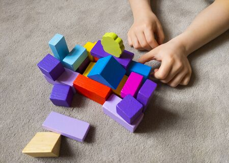 A child is playing withcolorful heart with colorful wooden building blocks. World autism awareness day concept.