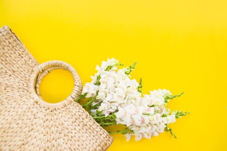 Fashionable straw bag with beautiful bouquet of white flowers on bright yellow background with copyspace. Stock Photo