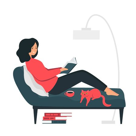 A young woman lies on a couch and reads a book. Room interior: a cat stretched out on a sofa, a stack of books lies on the floor, a floor lamp.