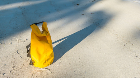 waterproof: Light and shadow on sandy beach with yellow waterproof bag