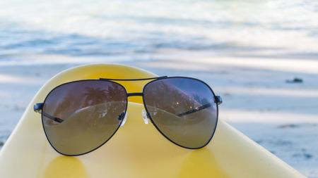 black white kayak: Black sunglasses on a yellow kayak and white beach background Stock Photo