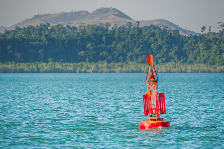 Red Marine signal light buoy in the sea.