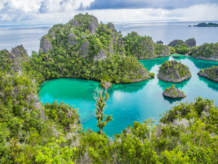 Wonderful island shape with forest, clear turquoise sea or lagoon and cloudy day