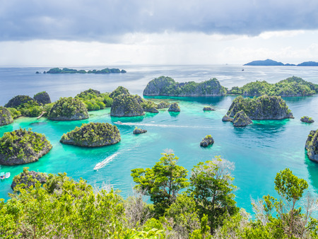 Wonderful island shape with forest, clear turquoise sea or lagoon, speedboats and cloudy day. Stock Photo