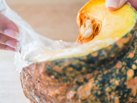 Pumpkin preparation for cooking concepts. Woman unwrap plastic from pumpkin that buy from supermarket.