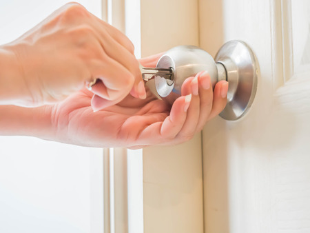 Woman with her two hands is unlocking the round door lock with the key for opening the door.  Stock Photo