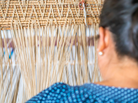 Wooden weaving loom and behind of weaver who weave the traditional cotton fabrics. Banco de Imagens