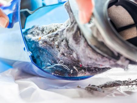 Primer plano de polvo en la caja de plástico de la aspiradora portátil o de mano.