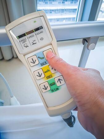 Closeup of woman 's hand pressing remote control button of electric adjustable hospital bed. Banque d'images - 133611658