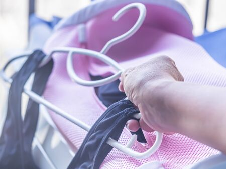 Woman's hand and stack of clothes hanger with black sports bras after laundry or washing process. Stock fotó