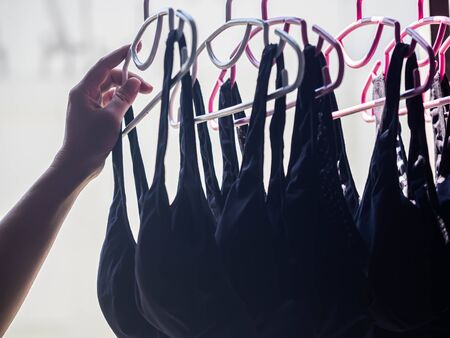 Woman 's hand and stack of clothes hanger with black sports bras after laundry or washing process.