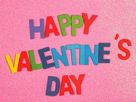 Top view or directly above angle of multicolored wooden alphabets or letters of happy valentine s day texts or words on rough gradient glitter pink paper texture and background. Love concepts. 写真素材