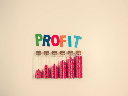 Cross processed tone effect. Multicolored wooden alphabet of profit text on light yellow pastel color background with small glass bottles, vivid or vibrant red gravel. Business growth concept. Imagens