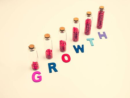 Multicolored wood alphabet of growth word with small glass bottle and red gravel. Imagens