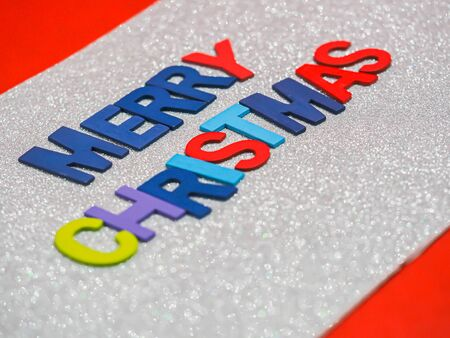 Multicolored wooden alphabet of Merry Christmas on glitter paper and red background. Imagens