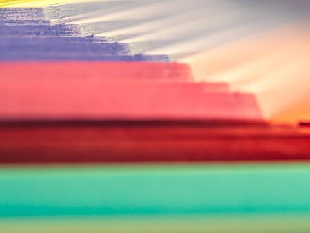 Abstract and closeup of pastel multicolored stacked paper background. Colorful and cheerful horizontal striped or steps pattern, rough and blurry texture.