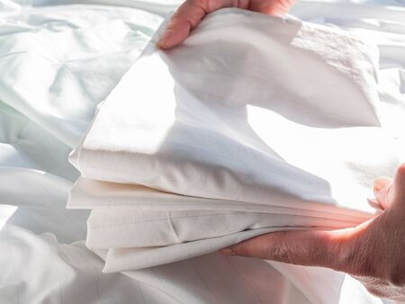Woman's hand with folded zippered dust mites pillow cover on wrinkle white bed cover on the bed in the bedroom.