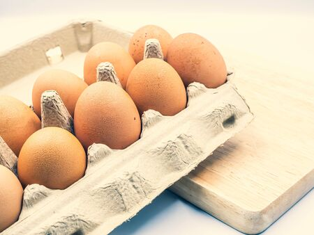 Closeup and cross processed tone of chicken brown eggs in paper carton tray on wooden cutting board in the kitchen. Cooking, dieting, healthy eating, nutrition and Easter holidays concepts and ideas. Banco de Imagens - 134336078