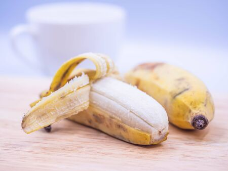 Closeup of peeled cultivated banana on wooden cutting board with blurry white coffee cup. Imagens