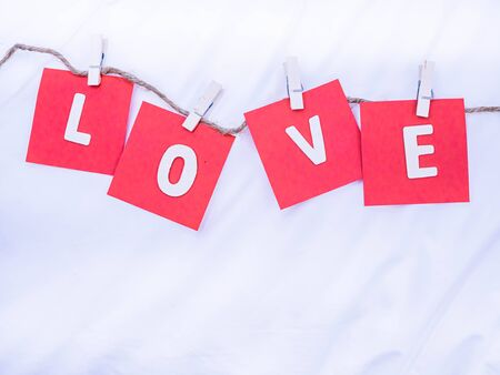 Top view wooden alphabets of love word,tweezers,red note paper and hemp rope on white wrinkle cotton fabric texture background for love, romance, valentine 's day,wedding, honeymoon concept and idea.