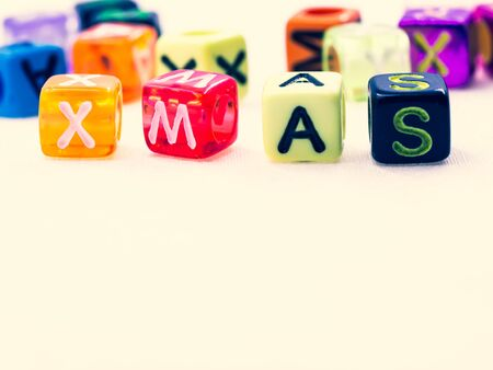 Closeup, macro photography of multicolored small plastic alphabet dice of Xmas word on white cross processed color tone background for holidays anniversary, celebration,greeting card concept a