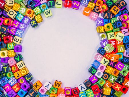 Top view or directly above of vivid colorful multicolored small plastic alphabet dice on white paper background. Copy space for education, kid learning concept and idea. Banco de Imagens