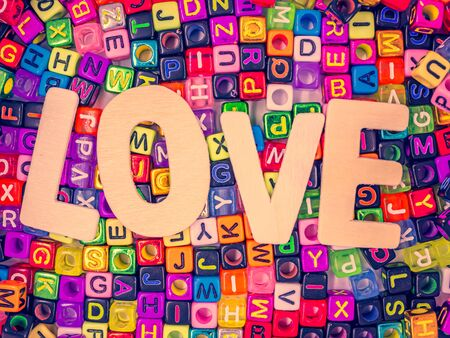Top view, cross processed tone of wooden alphabet love word on colorful multicolored small plastic alphabet dice background for love, romance, valentine's day, wedding, greeting card concept and idea.