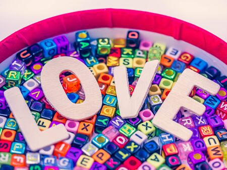 Cross processed of wooden alphabet love word on colorful multicolored small plastic alphabet dice background in paper box for love, romance, valentine's day, wedding, greeting card concept and idea. 写真素材