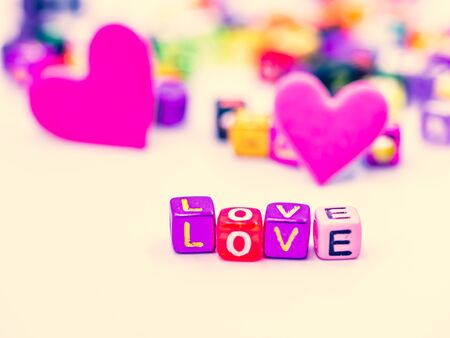 Cross processed tone, closeup, macro photography of colorful small plastic alphabet dice of love word on white background with blurry vivid, vibrant pink heart shape for love, romance, valentine idea.