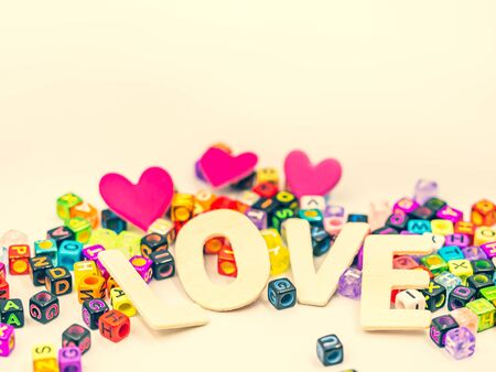 Cross processed tone wooden alphabet love word, colorful small plastic dice on yellow pastel color background with blurry vivid, vibrant pink heart shape for love, romance, valentine 's day idea. Imagens